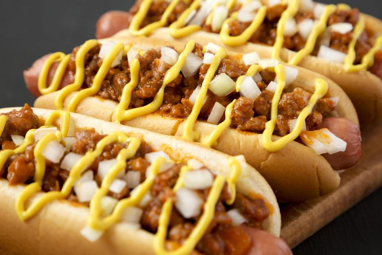 detroit style hot dog also known as the coney dog with beef chili, raw onions and mustard